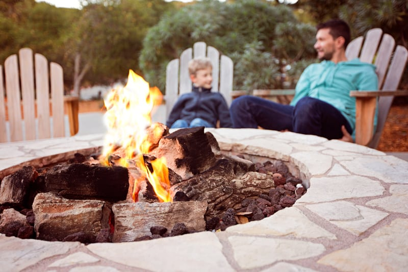 Man and Boy Sitting by a Fire Pit